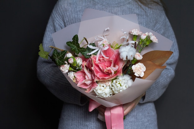 Девушка держит в руках оригинальный букет в винтажном стиле, приветствие фон или концепцию