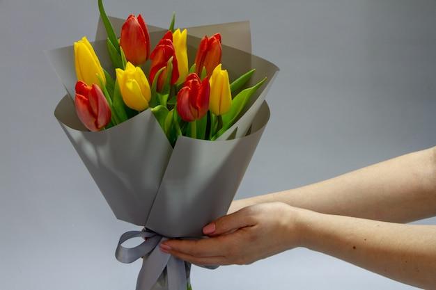 女の子の手が静物赤と黄色の未吹き付けのチューリップ、セレクティブフォーカスの花束を保持します。