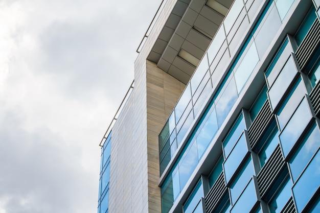 曇り空の反射と近代的なガラス建築高層ビル