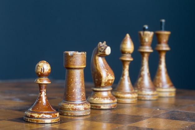 古いチェス盤のヴィンテージの木製のチェスの駒。