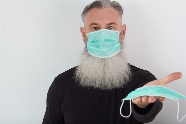 医療マスクで中年のひげを生やした男の肖像画。高齢者に対するコロナウイルスの危険性の概念。
