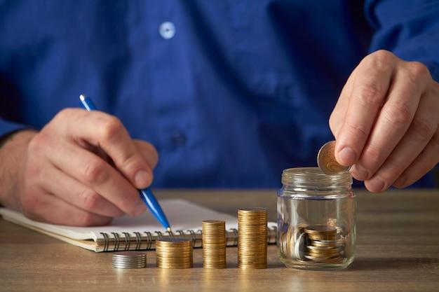 男は貯蓄を計算します。予算計画のコンセプト。オフィスで働くビジネスマン。男は瓶にコインを入れます。