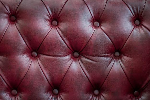 ビンテージの赤い革張りのソファのクローズアップの質感