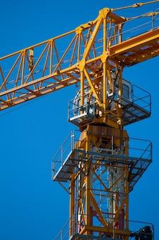 Желтый башенный кран работает над новым зданием