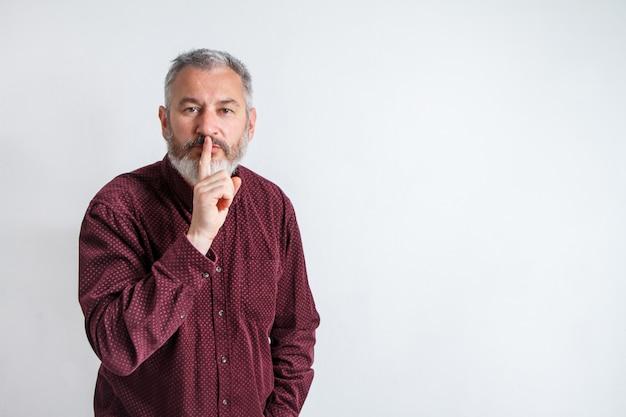 Серый бородатый мужчина показывает пальцем на губах