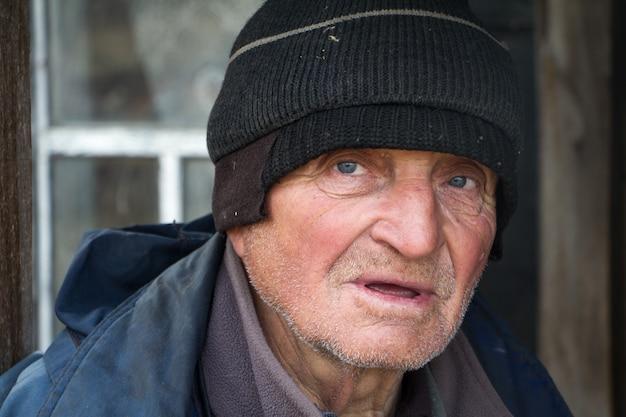 ずさんな服を着た老人は彼自身の台無しにされた家の敷居の上に立ちそして遠くを見る