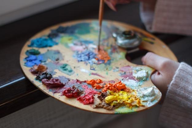 油絵を作成するへらでパレット上の塗料を混合する女性の手のクローズアップ