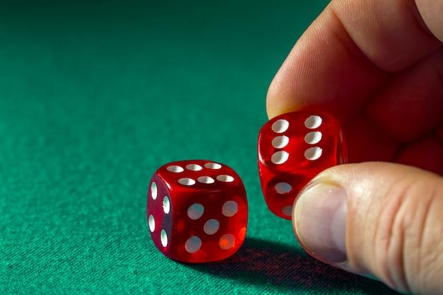 カジノの緑の布の上の勝利の組み合わせで赤いサイコロを持っている手のクローズアップ。