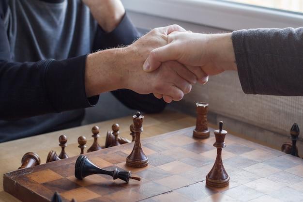 Старик пожимает руку сопернику в игре в шахматы