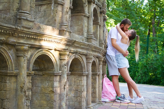ファッションの女の子とアイスクリームを食べると遊園地でお互いに笑顔アウトレット服の男