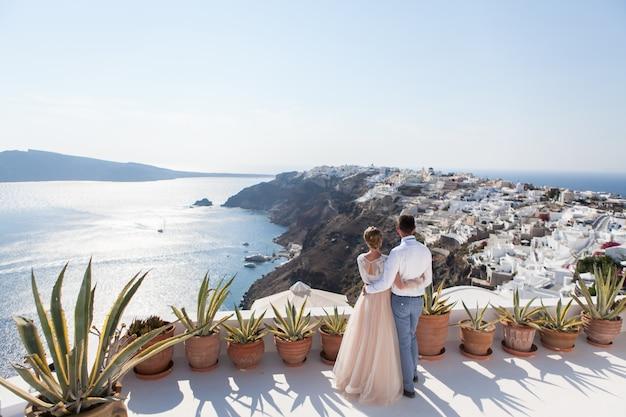 ギリシャの新婚旅行の月を海の上のテラスで楽しんでいる新婚者のカップル