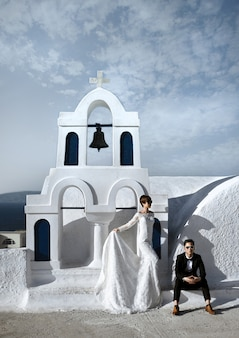 サントリーニ島、ギリシャのイアの村の古い白い教会でファッショナブルなエレガントな新婚カップル