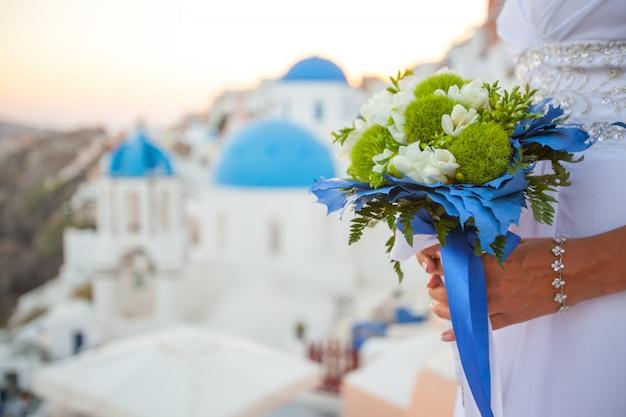 花嫁は白と緑の色と青い装飾のウェディングブーケを持っています。サントリーニ島、ギリシャに沈む夕日
