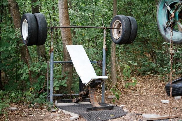 都市公園の太い木々の中で古いタイヤから大まかな自家製シミュレータのクローズアップ