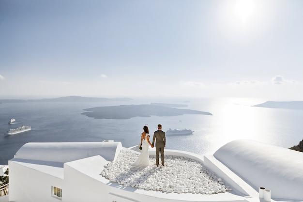 ギリシャの新婚旅行を海のテラスで楽しむ新婚カップル