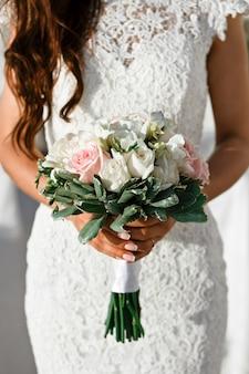 背景をぼかし、選択と集中に春のピンクと白の花のクローズアップブライダルブーケ