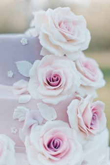 庭、選択と集中の背景をぼかした写真に現実的なピンクのバラで飾られたパステルカラーのウェディングケーキ