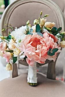 パステルカラーの新鮮な春と夏の花のクローズアップブライダルブーケは古典的な椅子の上に立つ
