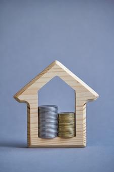 Деревянная фигурка дома и две колонки монет внутри на сером фоне.