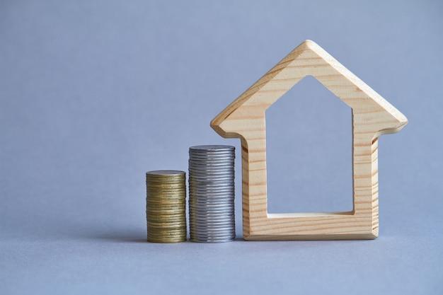 Деревянная фигурка дома с двумя колоннами монет рядом на сером фоне, концепция покупки или аренды здания, выборочный фокус