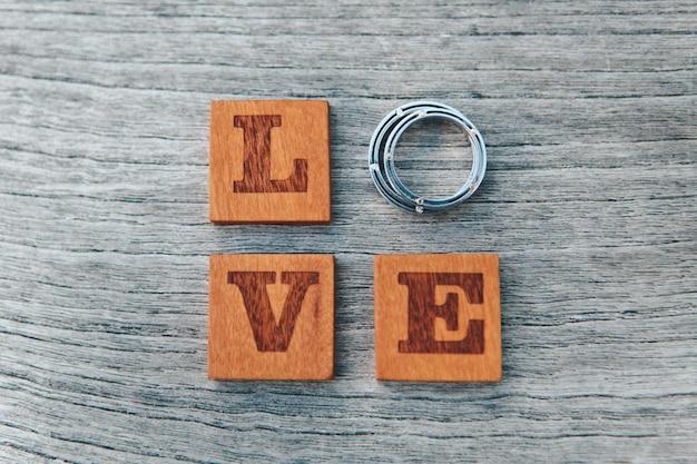 愛という言葉のクローズアップは、文字と結婚指輪で構成されています