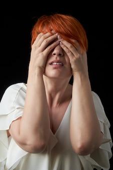 大人の赤髪の女性は彼女の手で目を閉じた