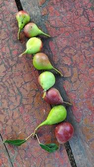 熟した赤緑梨のクローズアップ行は古いベンチにあります。