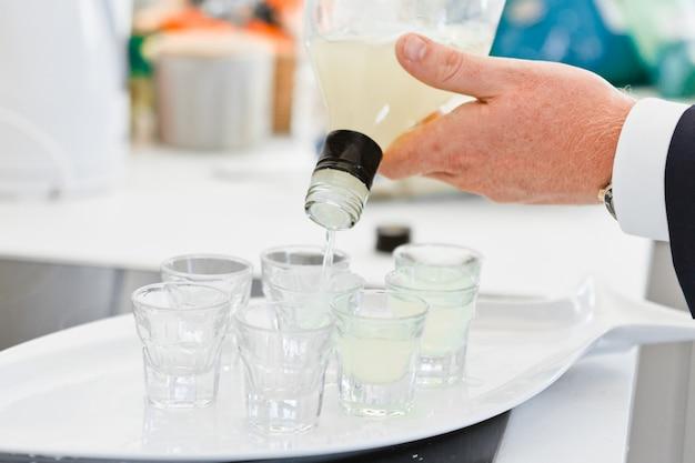 バーテンダーのクローズアップ手はショットグラスに飲み物を注ぐ