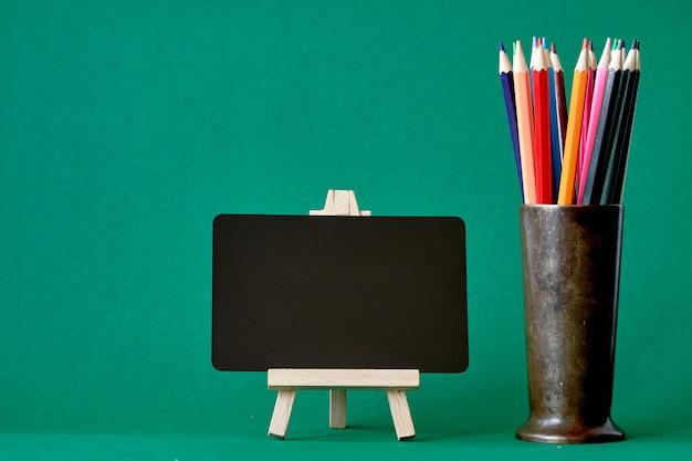 イーゼル上のミニチュアチョークボードと金属製のスタンドに色とりどりの鉛筆は、緑の背景、学校、選択と集中に戻る分離