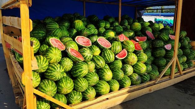 市場での緑のストライプスイカの大きな山