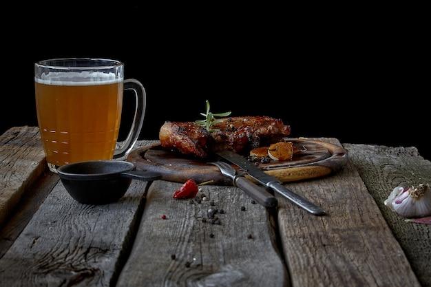 Натюрморт с большим жареным стейком, стаканом пива, горчицей и столовыми приборами на старой деревянной столешнице, концепция октоберфеста