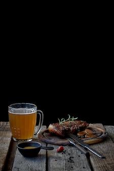 オクトーバーフェストのコンセプトである大きなフライドステーキ、ビール、マスタード、古い木製のテーブルの上のカトラリーのグラスのある静物