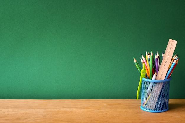 きれいな緑のチョークボードの背景に学校の机の上の学用品と青いガラスで学校に戻る