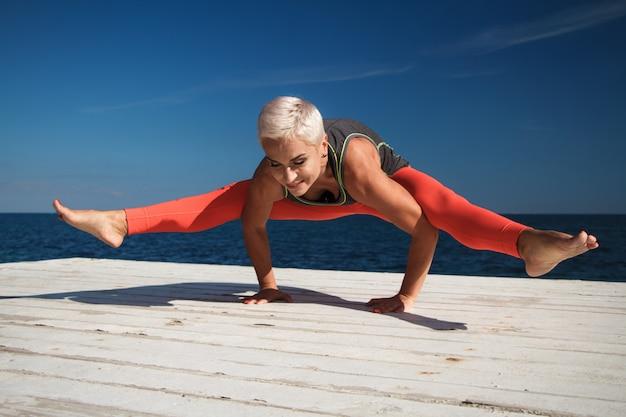 短い髪の大人の金髪の女性は、海と青空を背景に桟橋でヨガを練習します