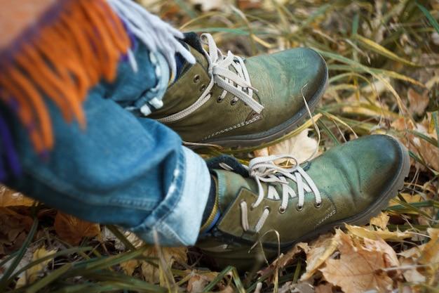 Закройте ноги в зеленых походных ботинках