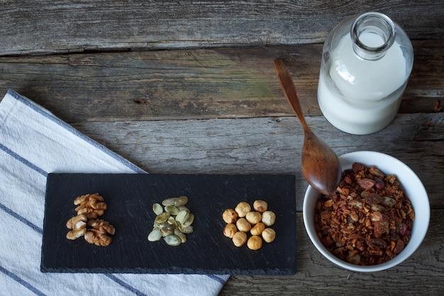 亜麻の種子、クランベリー、ミルクのボトル、テーブルの上の黒いスタンドにナッツのヒープとカリカリの蜂蜜グラノーラボウル