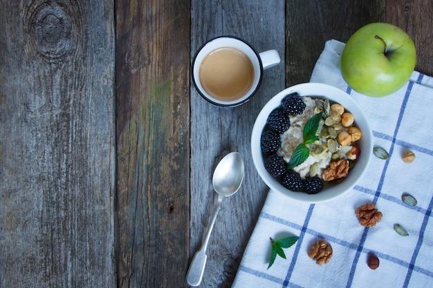 Вид сверху овсяная каша, кофе, яблоко, ягоды и орехи на деревянном столе