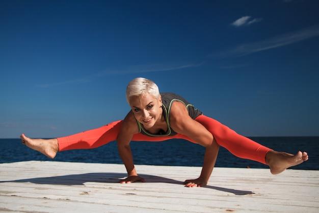 短い髪を切った大人の金髪女性が桟橋でヨガを実践