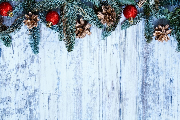 テキストのコピースペースを持つ白い木製の背景にクリスマスの装飾とトップビューモミ枝。