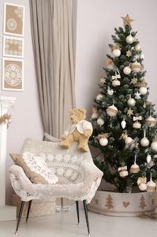 装飾されたクリスマスツリーの背景をぼかした写真の手作りニットラップで椅子の後ろにクローズアップグッズテディベア。