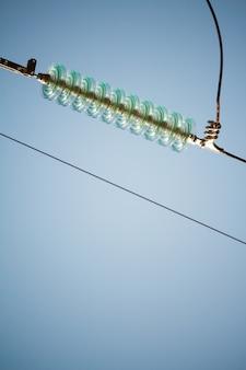 Крупным планом вид снизу изоляторов на высоковольтных проводах на силовой башне против голубого неба