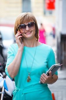 通りを歩いて、スマートフォンで話している彼女の手でドキュメントを持つ大人の中年ビジネス女性