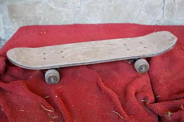 汚れた赤い表面に古いビンテージ木製スケートボード
