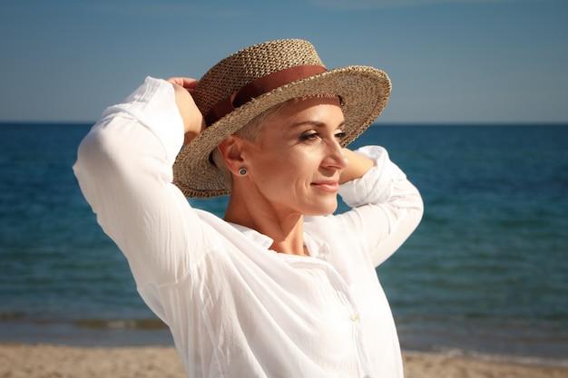 ビーチのビーチ帽子で短い髪を持つ素敵な若い女性