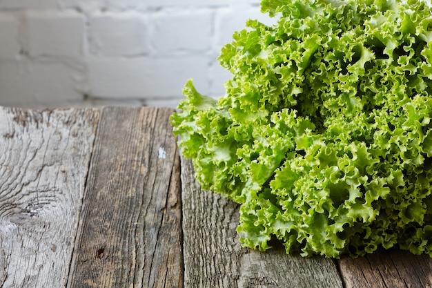 古い大まかな木製の表面にルートと緑の新鮮なサラダの頭