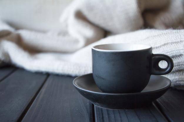 天然ウールテクスチャで作られた灰色のニットセーターにコーヒーとクローズアップ黒カップ