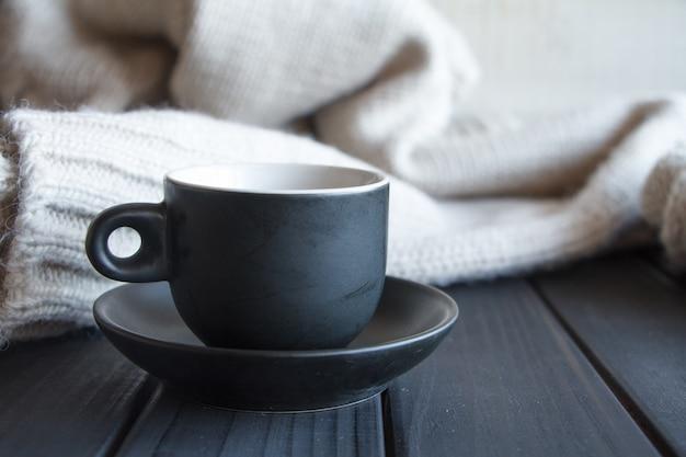 Чашка крупного плана черная с кофе на сером вязаном свитере из фактуры натуральной шерсти, волнистые складки,