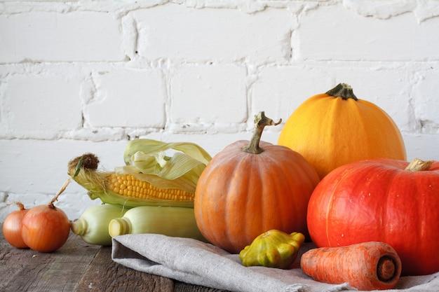 木製の感謝祭のテーブルに秋のカボチャと他の野菜