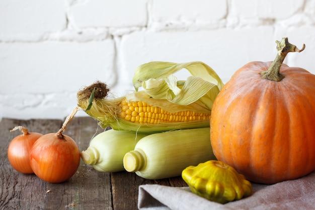 木製の感謝祭のテーブルにクローズアップ秋カボチャと他の野菜