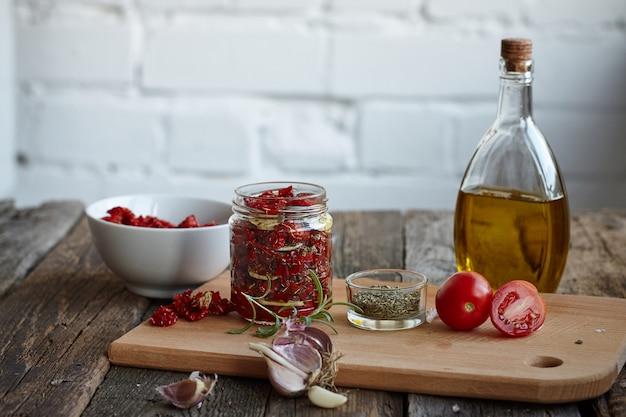 素朴な木製の表面にプロバンスハーブ、ニンニク、オリーブオイルを加えた天日干しトマト